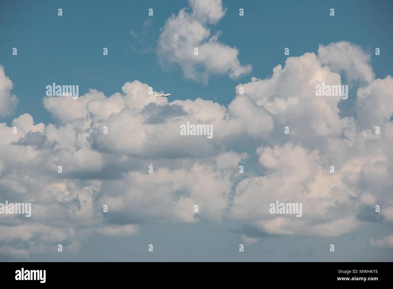 Kleines Flugzeug nähert sich in den blauen Himmel mit weißen Wolken Deutschland Stockbild