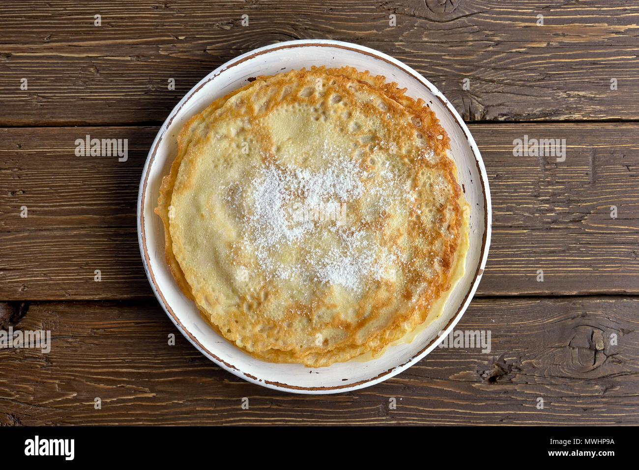 Dünne Pfannkuchen, süßen Crepes auf Holz- Hintergrund. Ansicht von oben, flach Stockbild