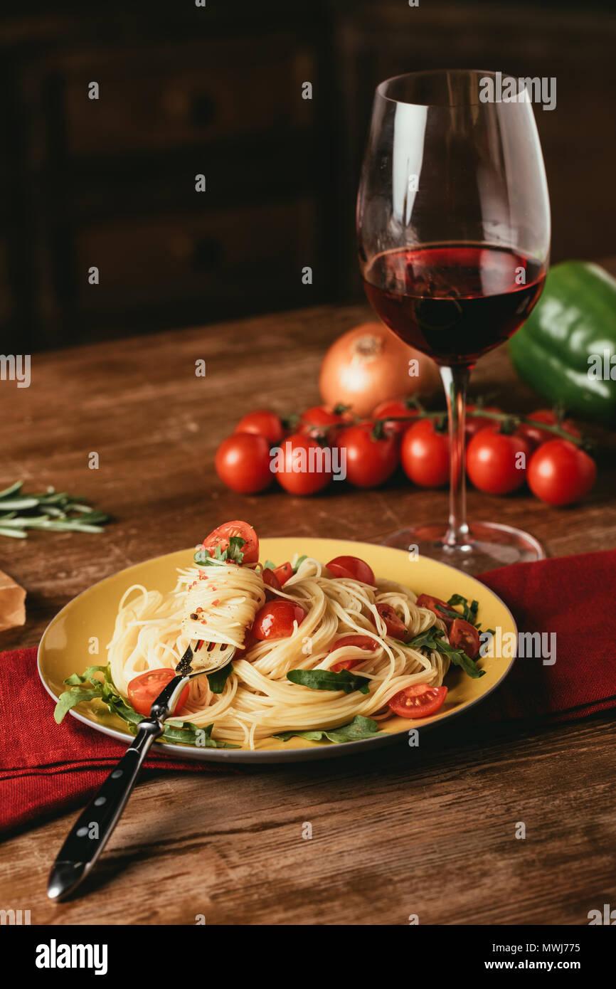 Traditionelle italienische Pasta mit Tomaten und Rucola in Blech und Glas Rotwein Stockbild