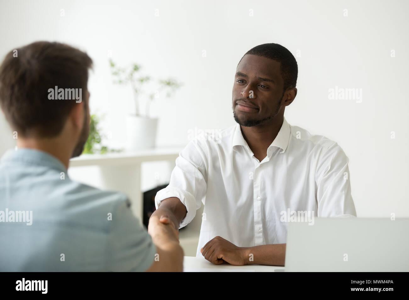 Froh, dass afrikanische amerikanische Arbeitgeber handshaking angestellt Kaukasischen Job ein Stockbild
