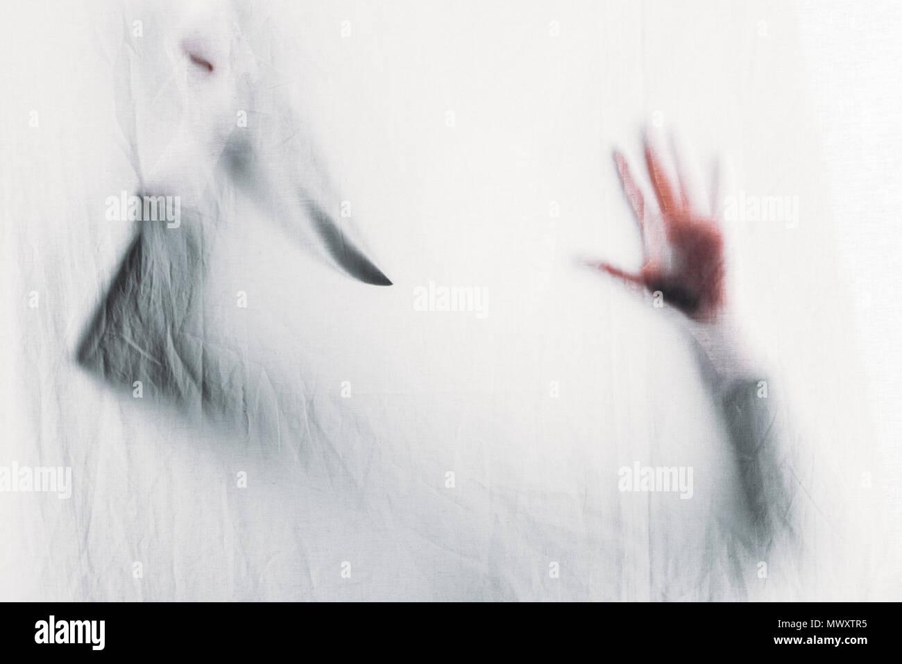 Beängstigend unscharfe Silhouette der unkenntlich Person holding Messer hinter Vorhang Stockfoto