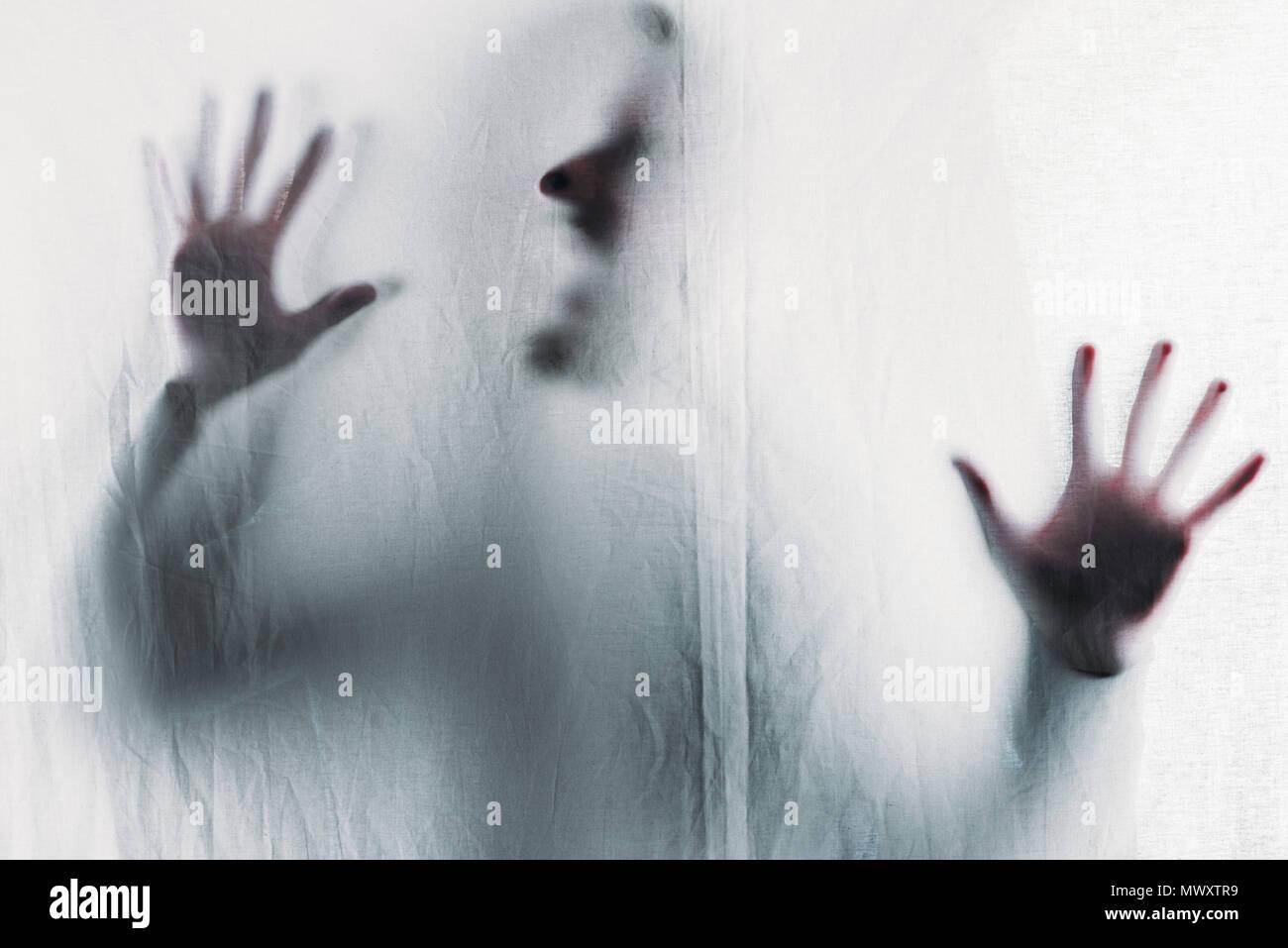 Beängstigend unscharfe Silhouette der unkenntlich Person hinter dem Schleier schreien Stockfoto