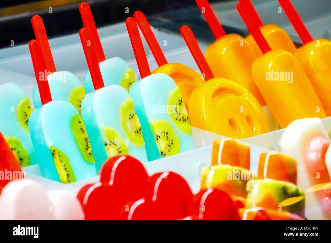Arrangiert Thirteen fruchtig; Kiwi, Erdbeeren, Berry, Drachenfrucht, Papaya, Mango, Minze, Schokolade, Milch, Orange, Ananas Eis stick, in froz eingefroren Stockbild