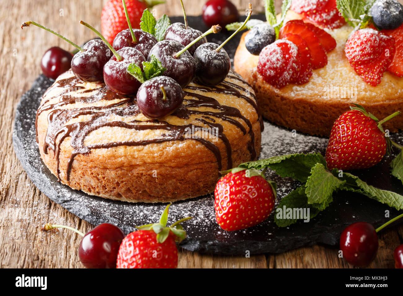 Dessert Kuchen mit Schokolade, Minze, Erdbeeren, Kirschen und Heidelbeeren close-up auf dem Tisch. Horizontale Stockfoto