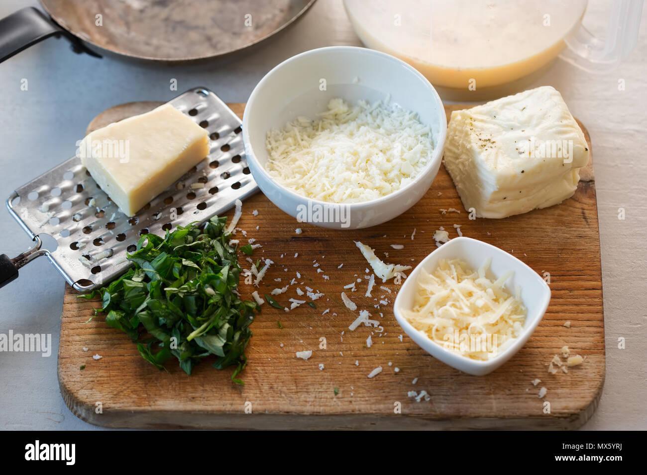 Frittata Zutaten: Verquirlten Eier & Milch, halloumi und Parmesan, schneiden Basilikum Stockbild