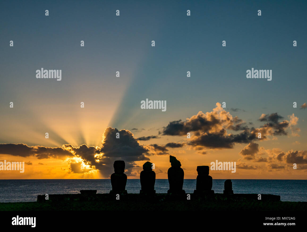 Dramatische bunt orange Sonnenuntergang und sunburst Licht mit Ahu Tahai, Moai Silhouetten, Hanga Roa, Rapa Nui, Chile Stockbild