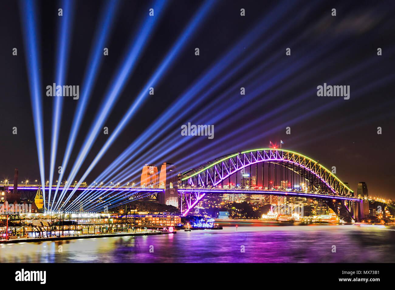 Vivid Sydney Festival des Lichts und der Ideen in der Stadt Sydney CBD um Hafen mit Lichtstrahlen aus der Harbour Bridge vom Circular Quay. Stockbild