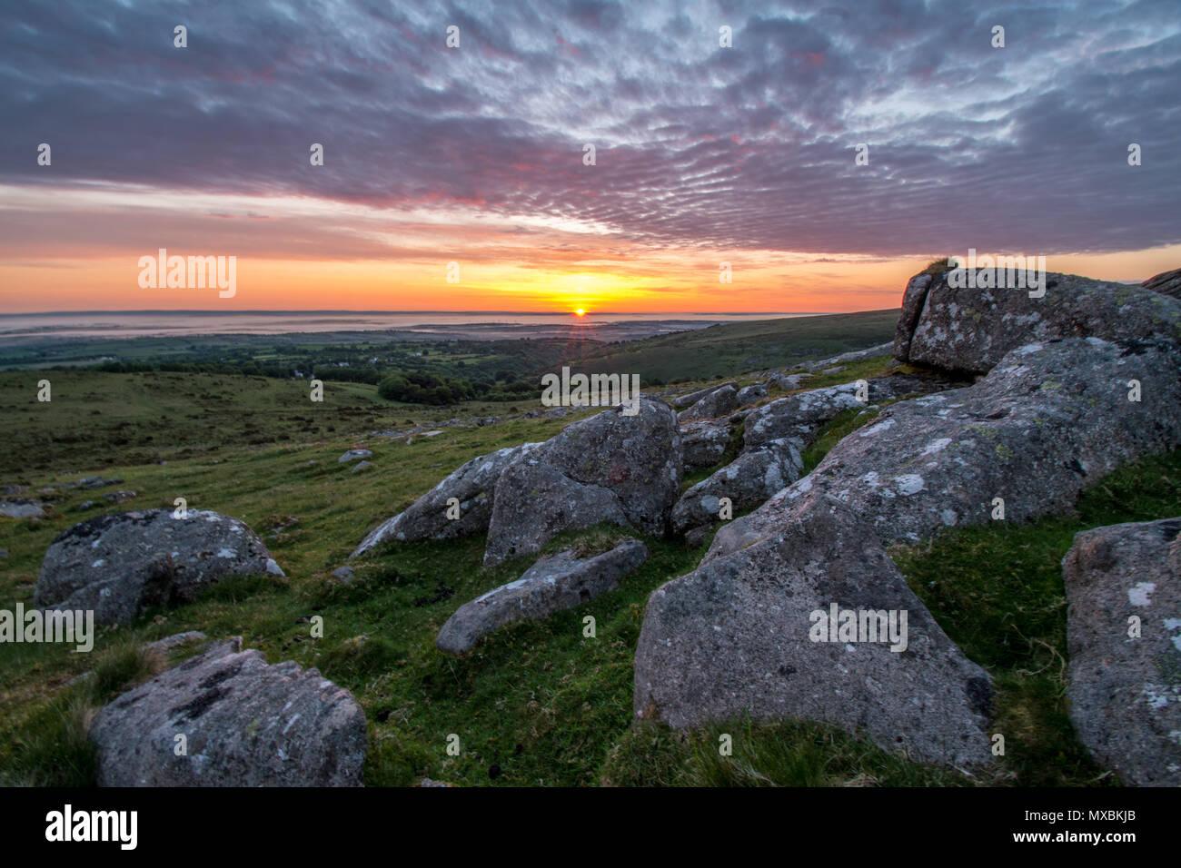 Einen schönen Sonntag morgen Juni Sonnenaufgang über dem Dorf Belstone in Dartmoor Stockfoto