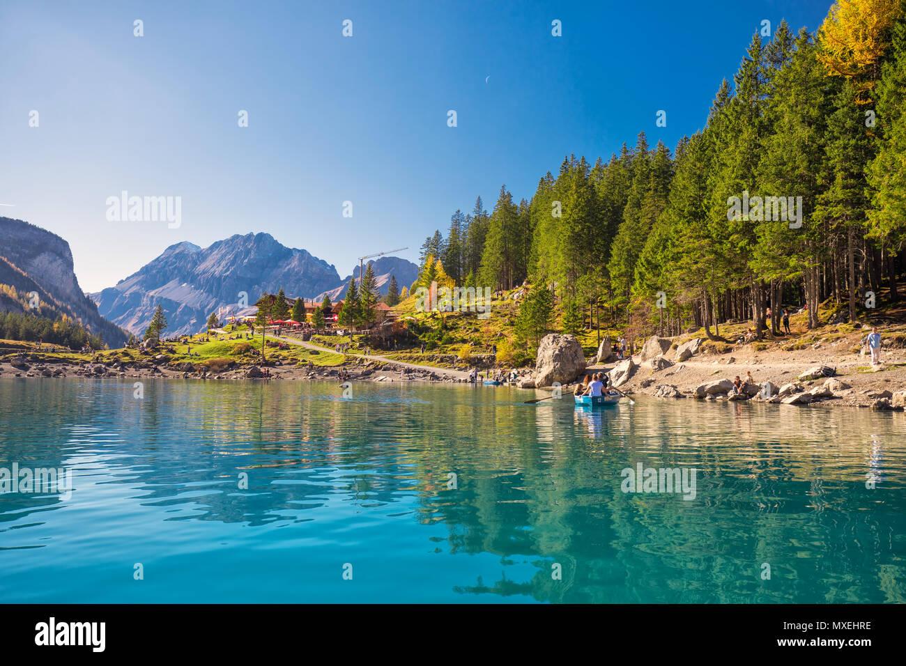 OESCHINENSEE, SCHWEIZ - Oktober 2017 - Amazing tourquise Oeschinnensee mit Wasserfällen, Chalet aus Holz und Schweizer Alpen, Berner Oberland, Schweiz Stockbild