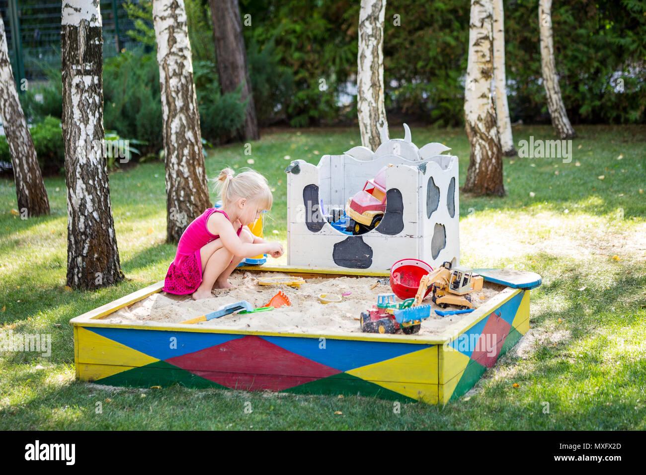 kleinen niedlichen baby mädchen spielen in holz- sandkasten. kind