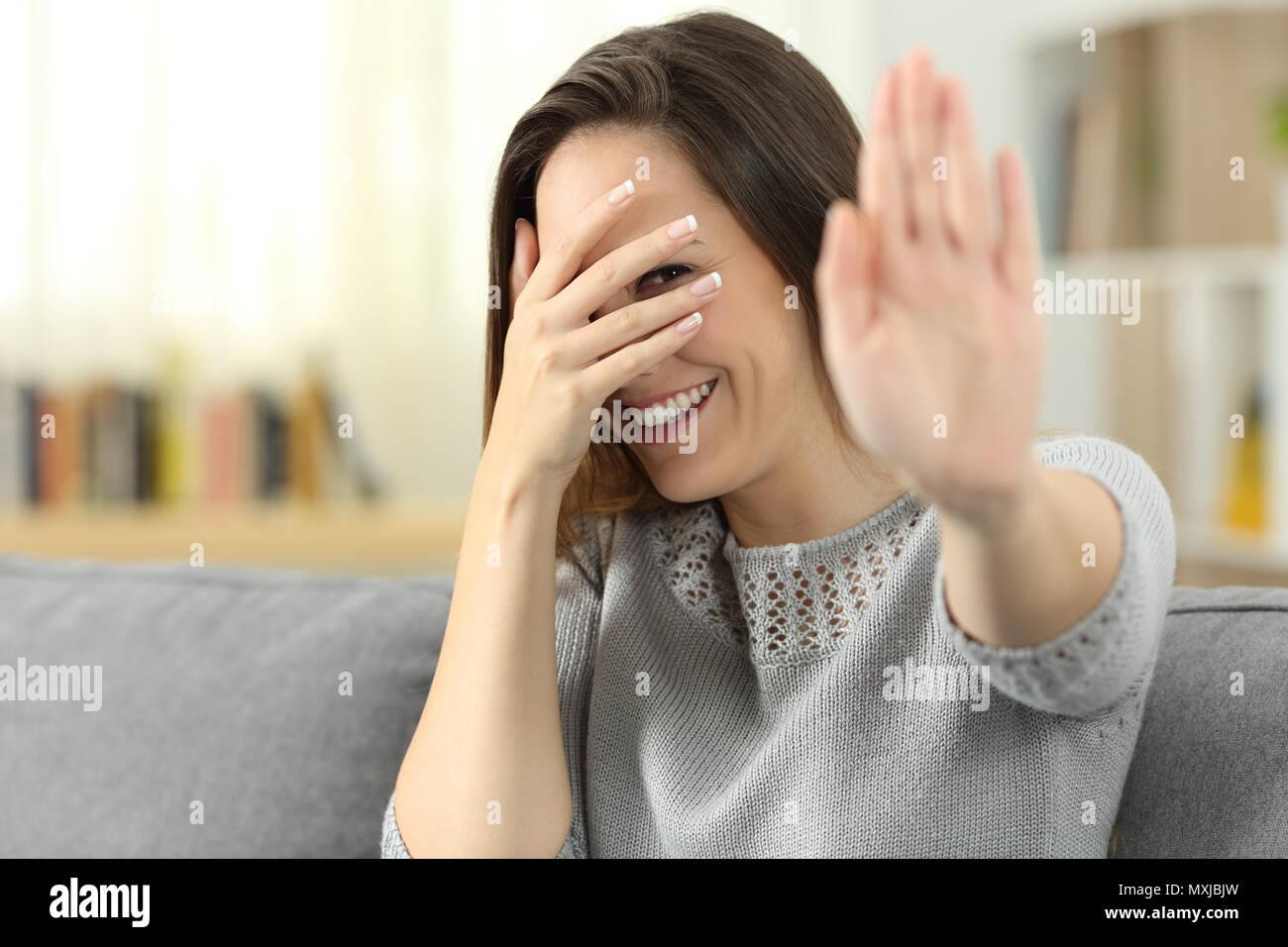 Schüchterne Frau versteckt sich das Gesicht mit der Hand auf einer Couch im Wohnzimmer zu Hause sitzen Stockbild