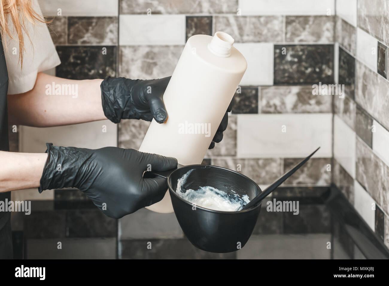Haarstilist gießen ein Oxidationsmittel Sahne in die Schüssel Vorbereitung einer färbenden Farbstoff Stockbild