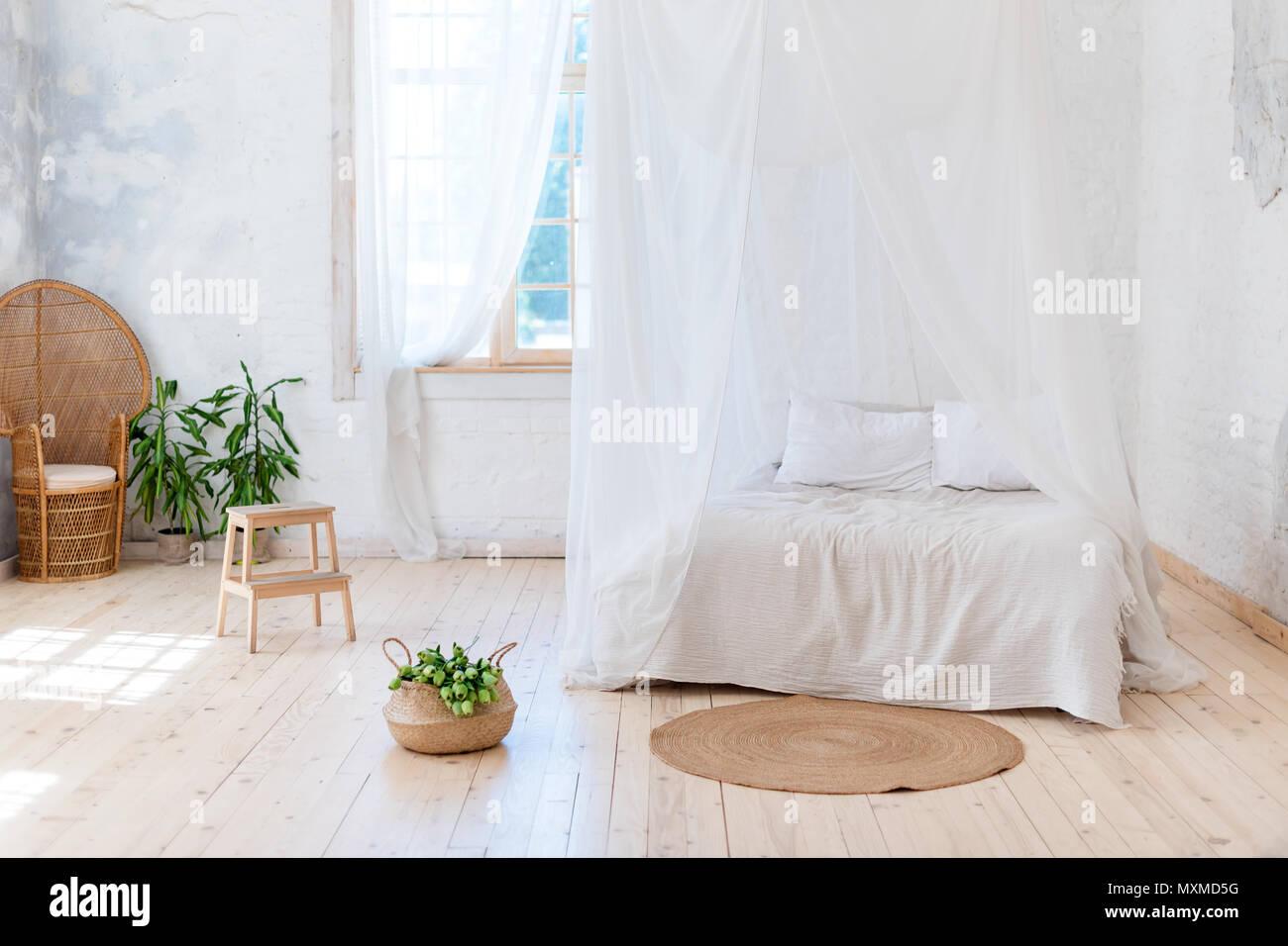 Gemütliches Schlafzimmer in hellen Farben mit Holzfußboden, ein ...