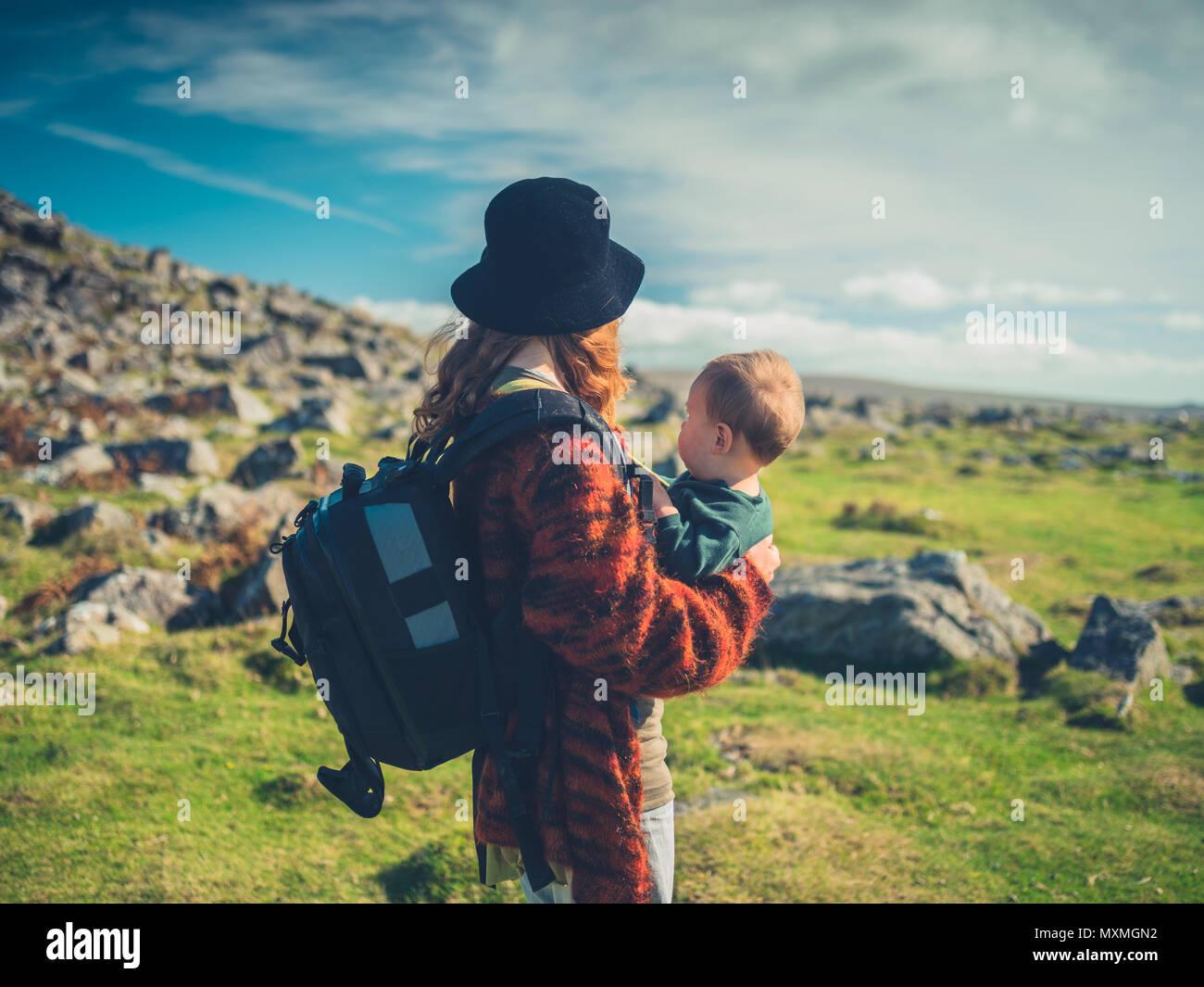 Eine junge Mutter mit einem Baby und einem großen bacpack ist Trekking durch die Wüste Stockbild