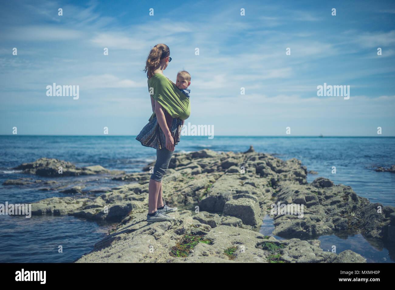 Eine junge Mutter an der Küste mit ihrem Baby im Tragetuch Stockbild