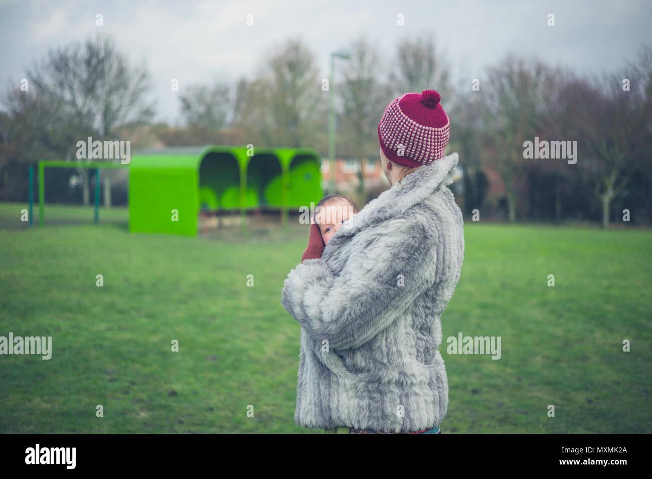 Eine junge Mutter steht auf dem Gras in einem Park im Winter mit ihrem Baby in einem Träger Schlinge Stockbild