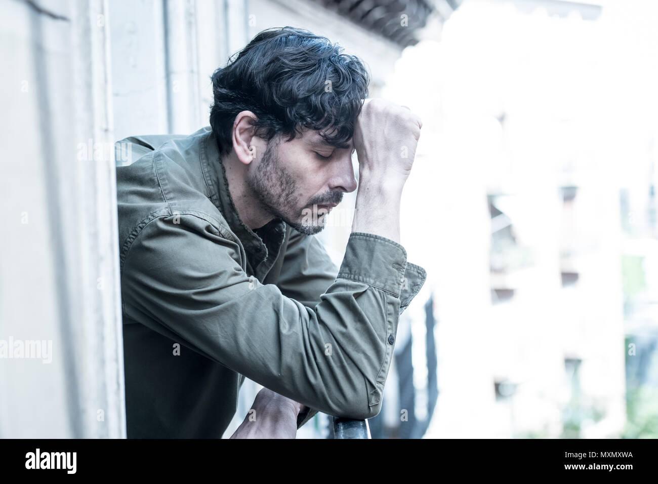 Nahaufnahme Portrait von traurig und deprimiert Mann schauen aus dem Fenster, auf dem Balkon zu Hause leiden Depressionen und Holzeinschlag einsam in der psychischen Gesundheit anhand von quantitativen Simulatio Stockbild