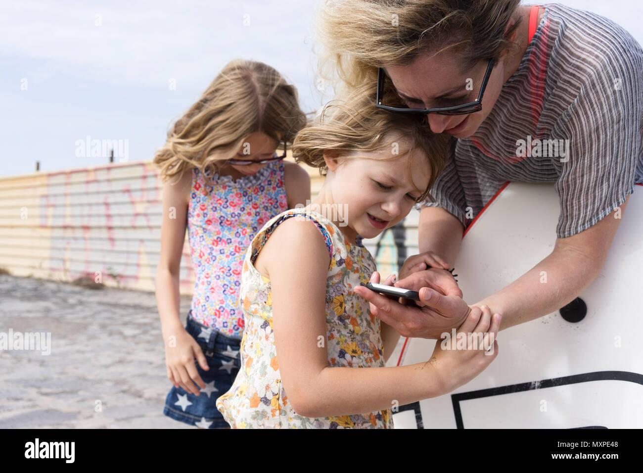 Die Mutter, die ihre Tochter etwas auf ihr Mobiltelefon mit der anderen Tochter im Hintergrund Stockbild