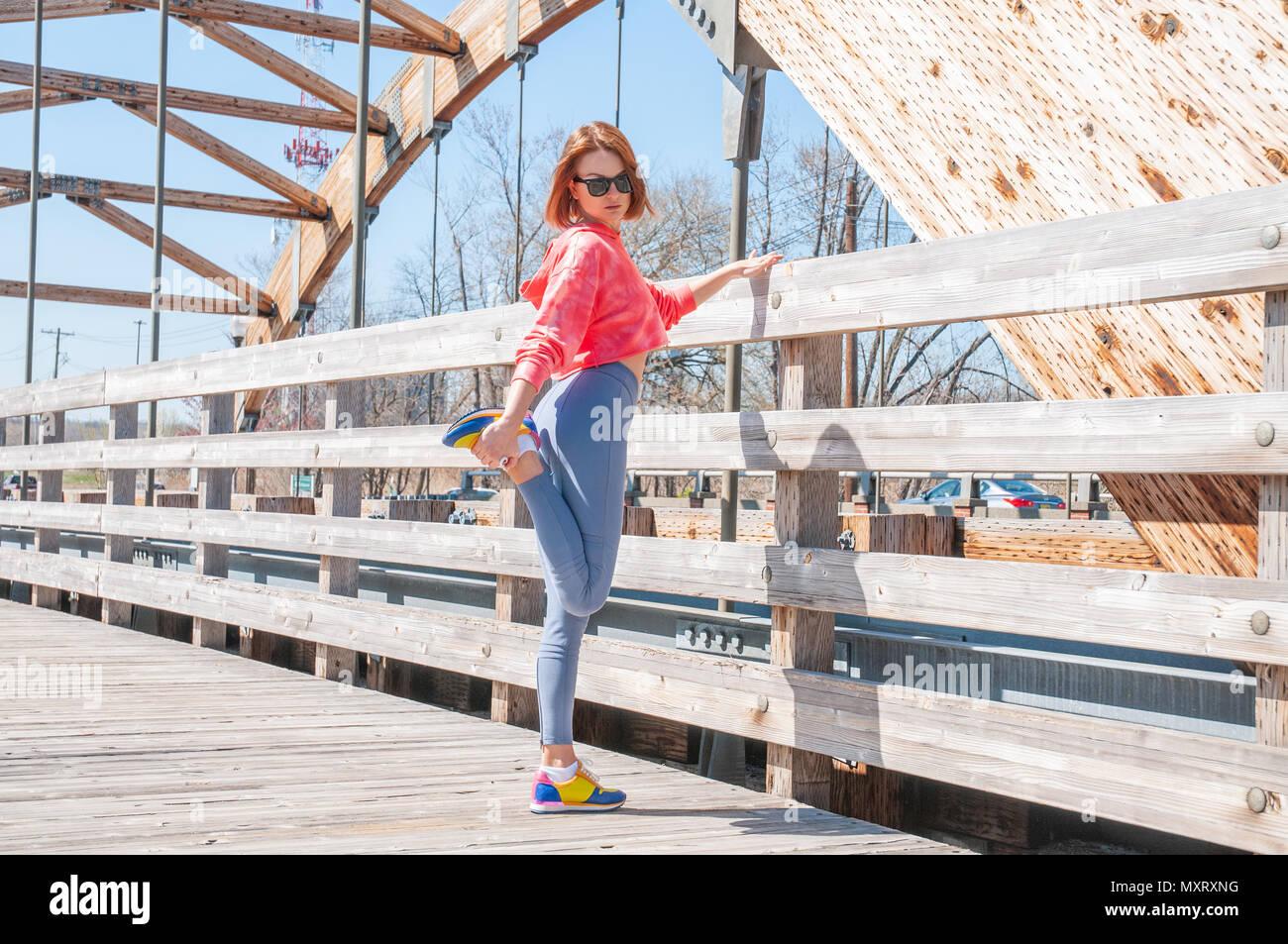 Athletische Frau dehnen ihre Beine im Freien vor dem Ausführen Stockbild