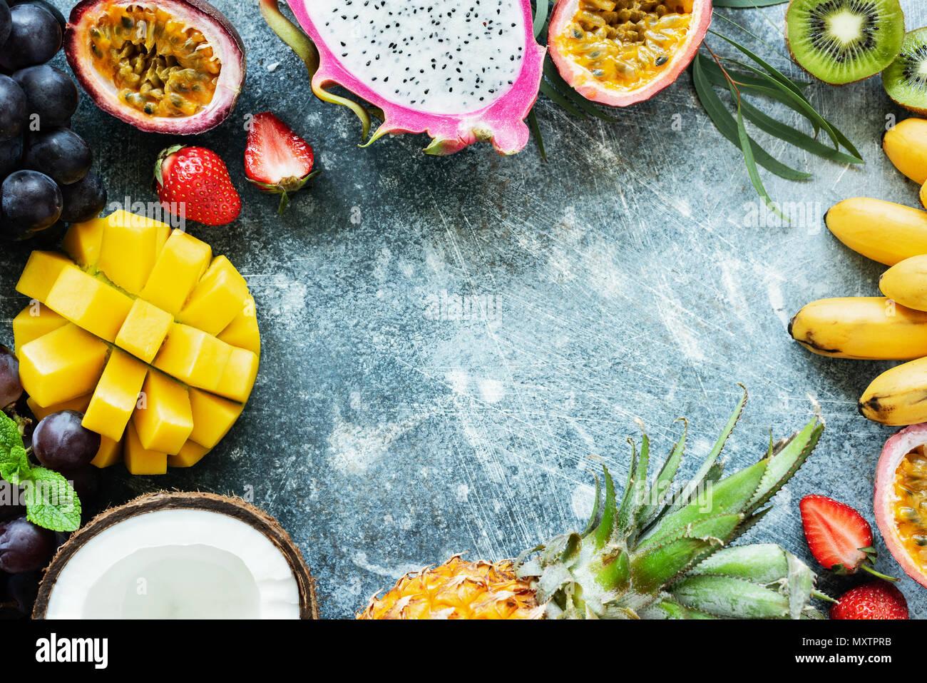 Rahmen aus frischen tropischen Früchten auf konkreten Hintergrund mit Kopie Platz für Text, Ansicht von oben. Konzept der Sommer, exotische Früchte, vegan und paleo Diät Stockbild