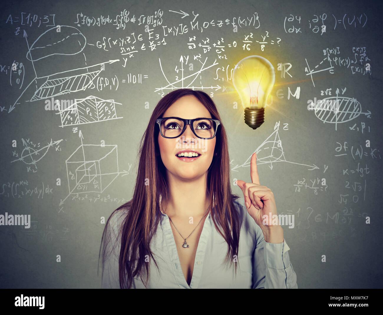 Ziemlich smart Brünette in Gläsern nach oben in die Erleuchtung der Lösung und kreative Idee Stockbild
