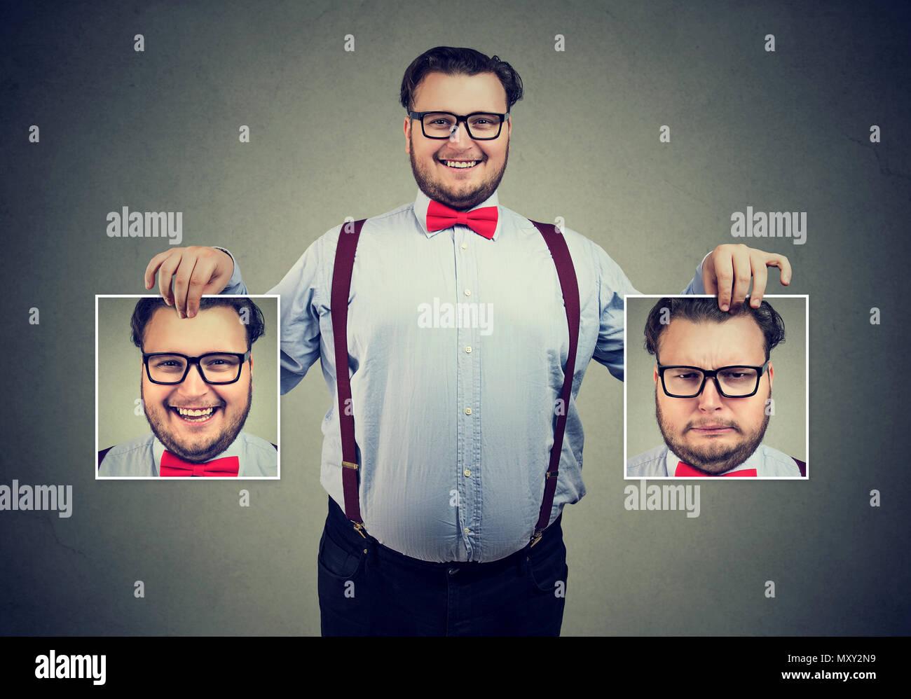 Junge fröhliche Mann in Gläser mit Bildern in der Hand, mit guten und schlechten Gefühle in Stimmungsschwankungen und lächelnd an Kamera Stockbild