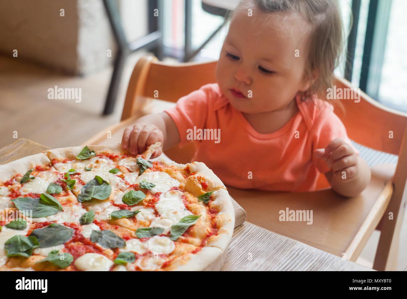 Baby Mädchen essen Pizza im italienischen Restaurant, gesund, ungesundes Essen, Kinder fast food Stockbild