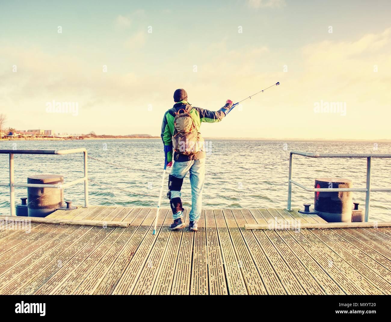 Wanderer mit Medizin Krücke und Bein in wegfahrsperre Spaziergang auf Wharf Pier fest. Man hat feste gebrochenes Bein in Gips. Happy deaktiviert man am Strand spazieren. Len Stockbild