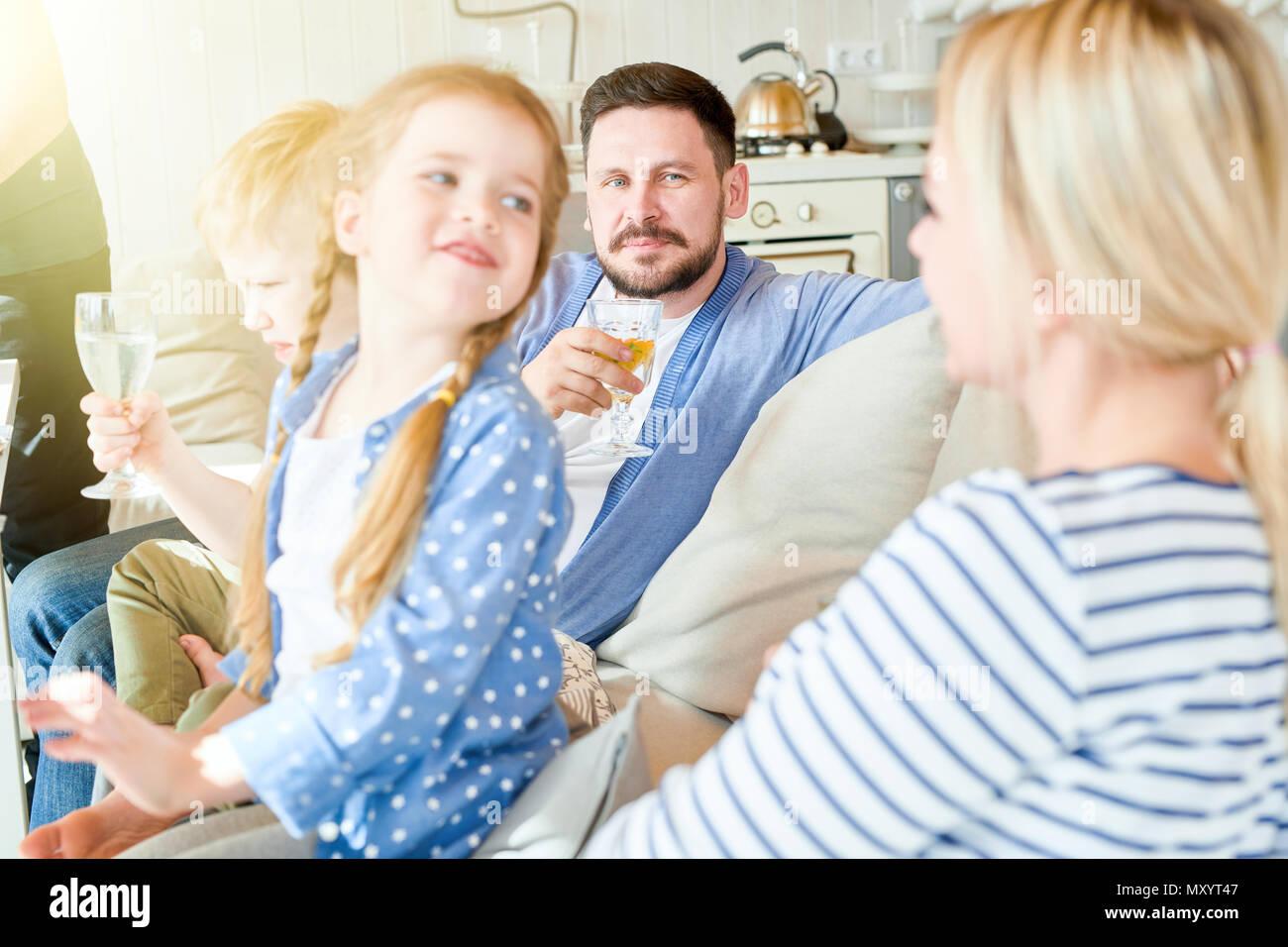 Portrait der glücklichen Familie mit zwei Kindern auf der Couch genießen festliche Dinner Party, zu Hause zu sitzen, auf der niedlichen rothaarigen Mädchen drehen an ihrer mo zu schauen Fokus Stockbild