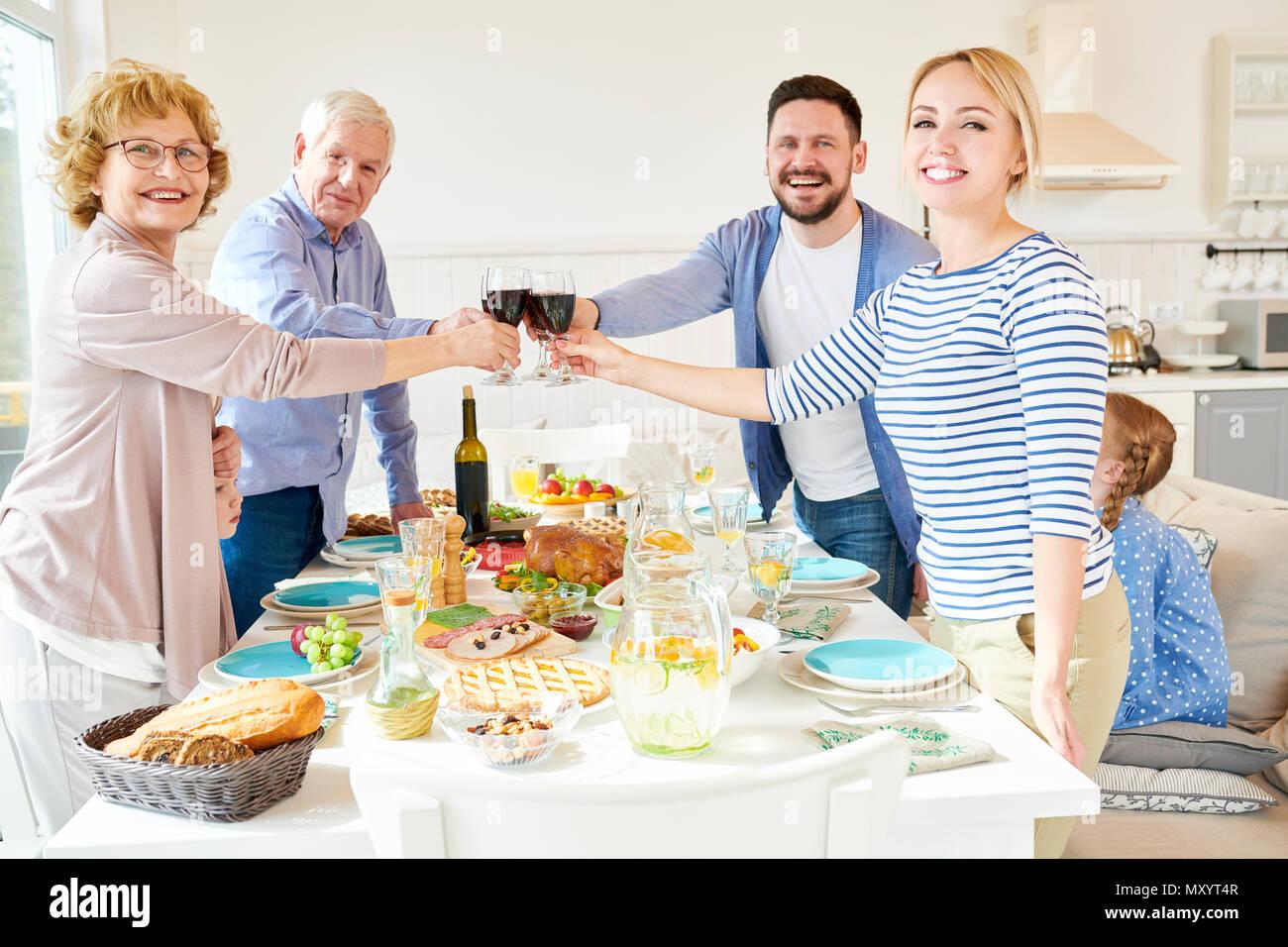 Portrait von glückliche zwei Generation Familie Abendessen zusammen Anstoßen über festliche Tafel mit köstlichen Gerichten und lächelnd an, Ca Stockbild