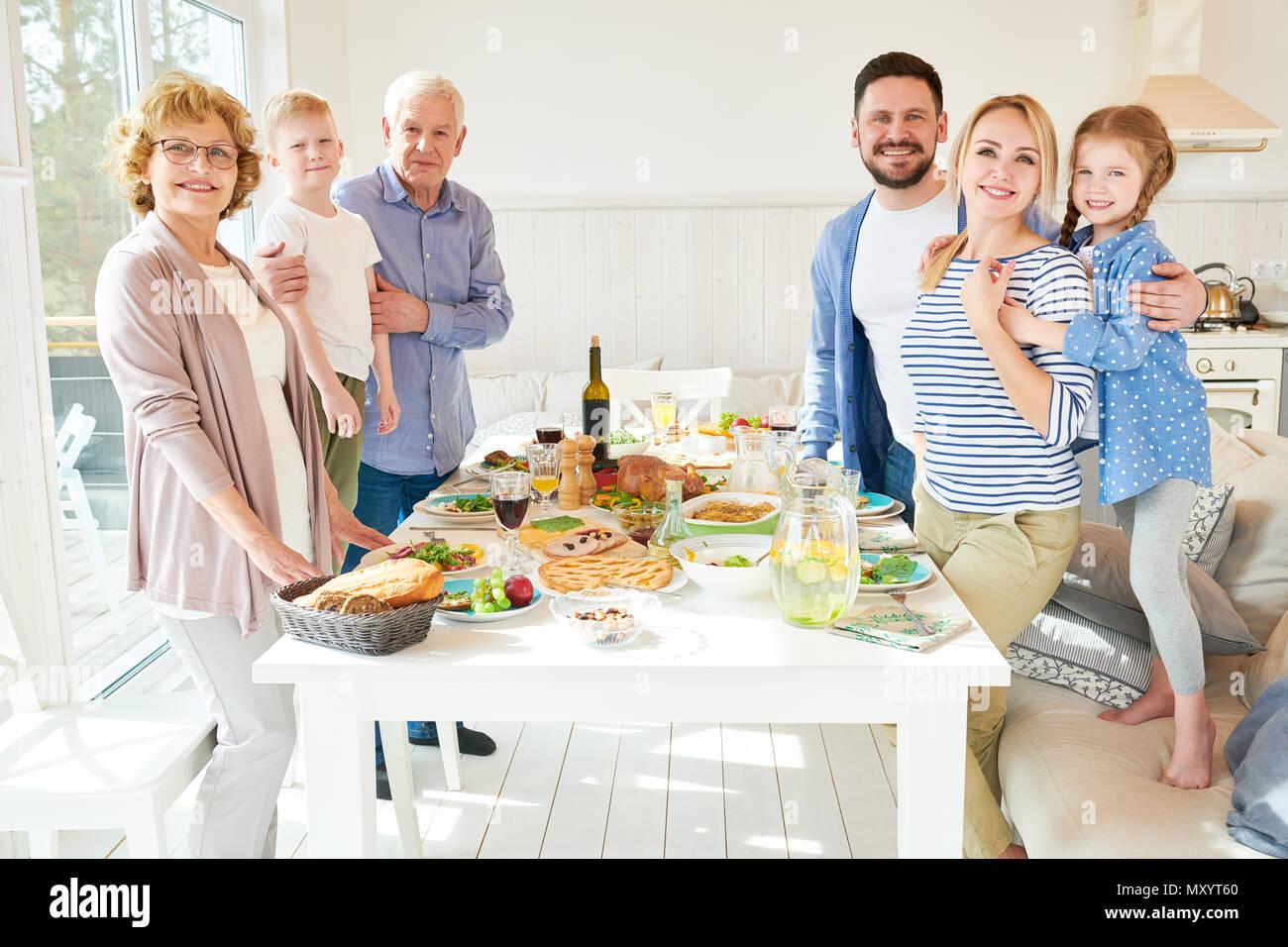 Portrait von glückliche zwei Generation Familie Abendessen zusammen posieren Runde festlichen Tisch mit leckeren Gerichten und lächelnd in die Kamera in der modernen Sun Stockbild