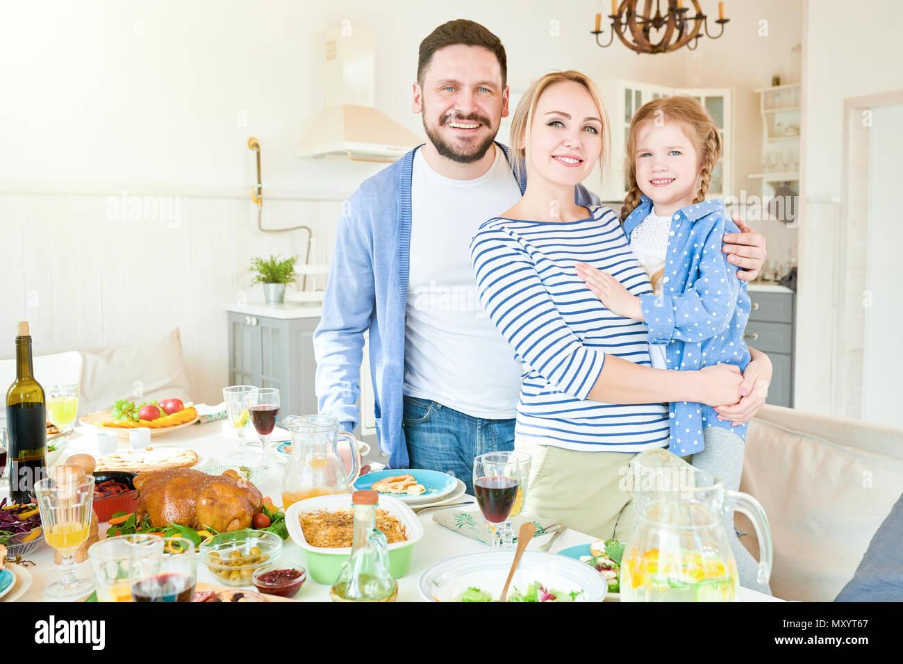 Porträt der glückliche junge Familie mit niedlichen kleinen Mädchen stehend an festlichen Abendessen mit köstlichen Gerichten und lächelnd an der Kamera in das moderne Apartment Stockbild