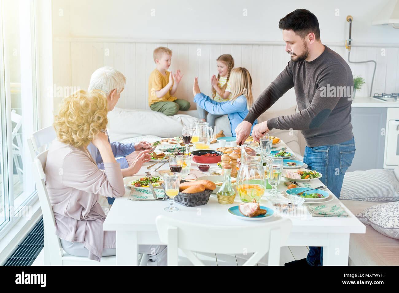 Portrait von Happy Family geniessen gemeinsam das Abendessen im Speisesaal mit festlichen Tisch in der modernen lichtdurchfluteten Wohnung sitzen, Platz kopieren Stockbild