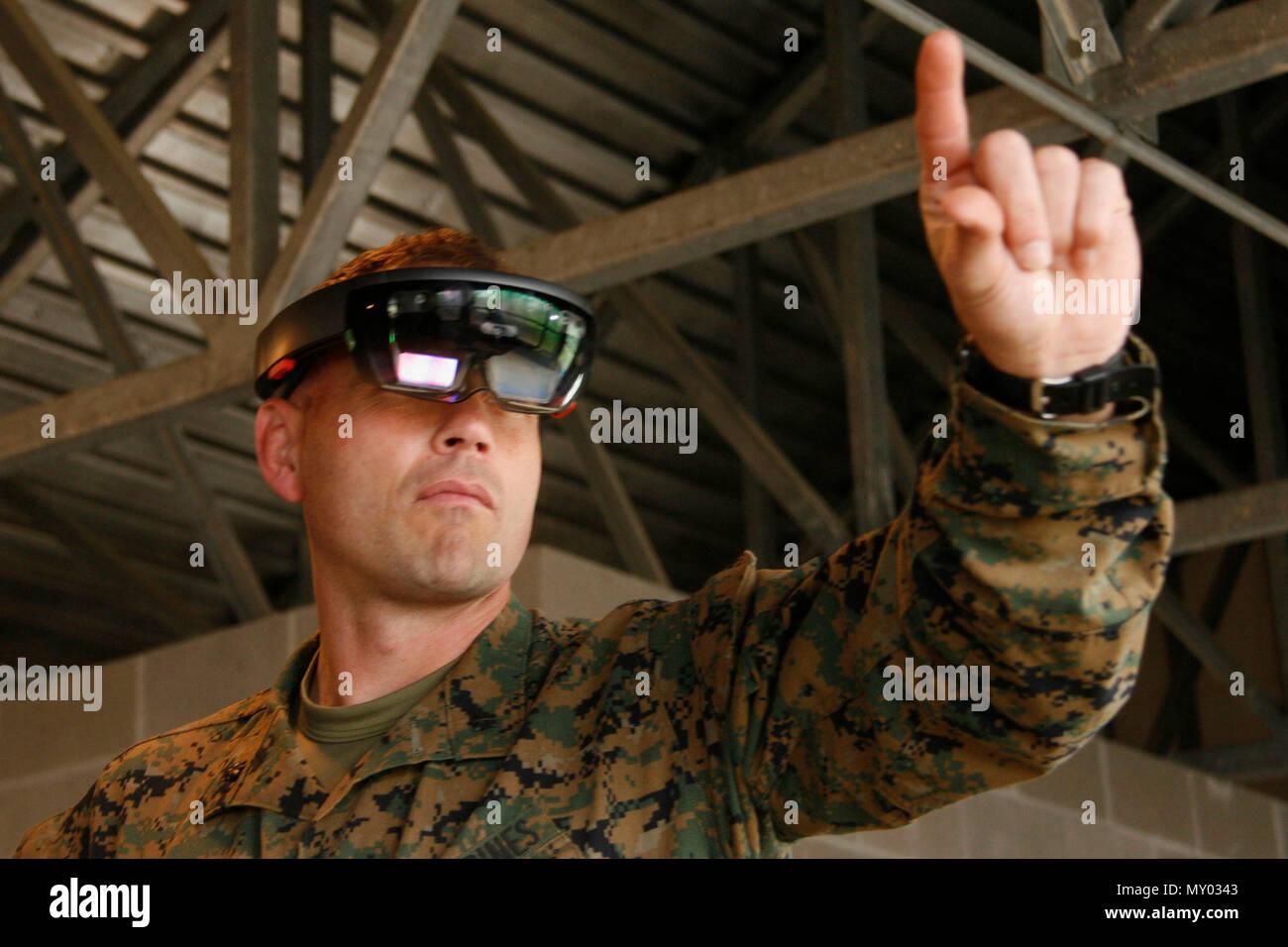 Us Marine Corps Oberstleutnant Marcus Mainz, Bataillonskommandeur, 2.BATAILLON, 6 Marine Regiment, 2nd Marine Division (2d MARDIV), zeigt, wie ein Training simulation Gerät in Camp Lejeune, N.C., Dez. 13, 2016. Generalleutnant John E. Wissler, Kommandierender General, US Marine Corps Forces Command, und Sgt. Maj. Christopher G. Robinson, befehlen Sergeant Major, US Marine Corps Forces Command, besucht eine dienststellenübergreifende Industrie Schulung Simulation und Ausbildung Konferenz kurz auf die verschiedenen Möglichkeiten der virtuellen Ausbildung. (U.S. Marine Corps Foto von Pfc. Michaela Gregory, 2d MARDIV C Stockbild