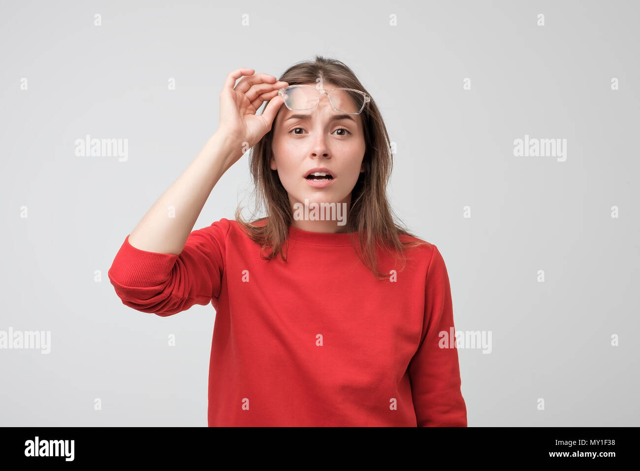 Junge kaukasier Frau Brille an Kamera mit Zweifel und Misstrauen auf der Suche Stockbild