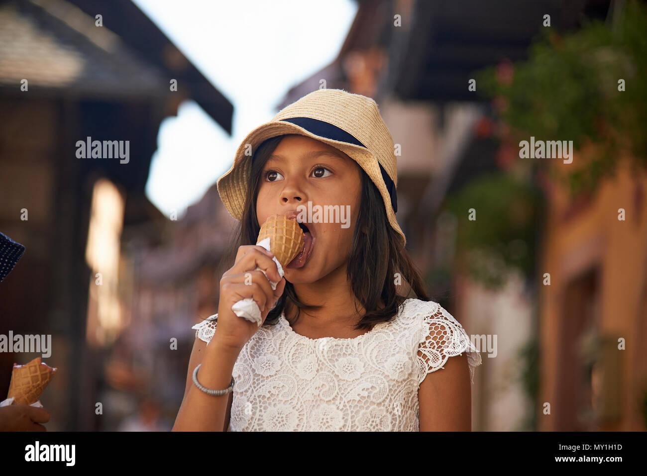 Kleinen Niedlichen asiatische Mädchen mit einem Strohhut essen Eis, während in den Urlaub im Elsass im Sommer Sonnenschein an einem heißen Tag Stockbild