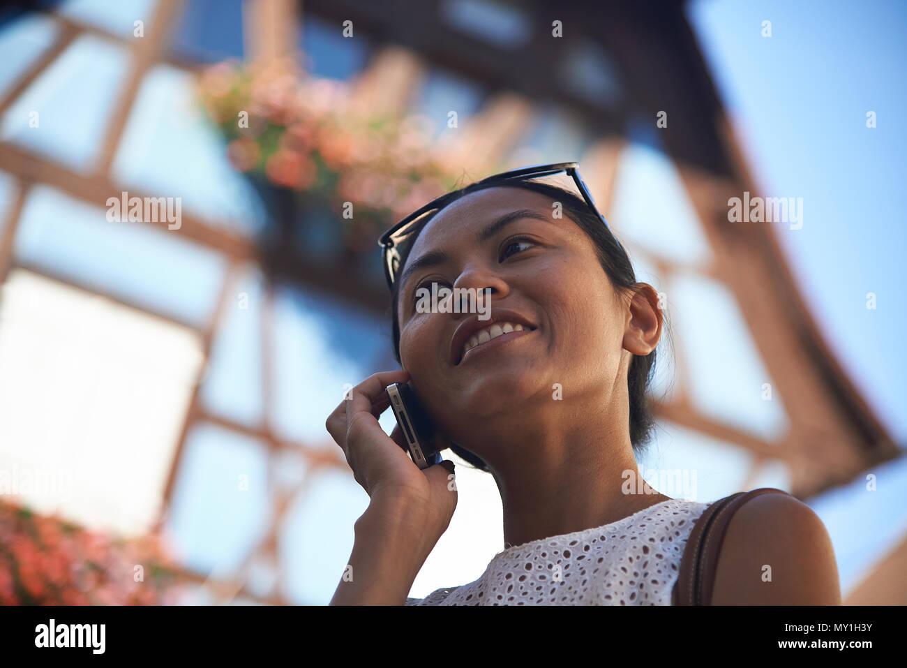 Hübsche asiatische Frau zu Fuß durch die Straßen in einem typisch französische Stadt in der Region Elsass im Gespräch auf ihr Handy, um Fotos zu machen und Suchen Stockbild