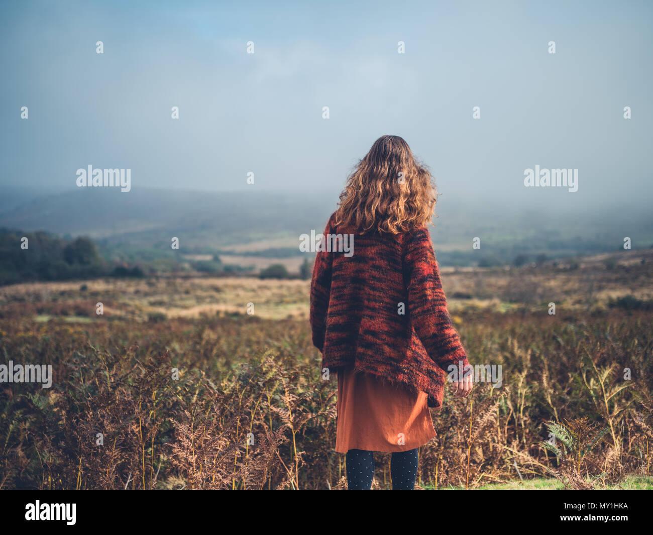 Eine junge Frau steht auf einem Moor im Herbst Stockbild