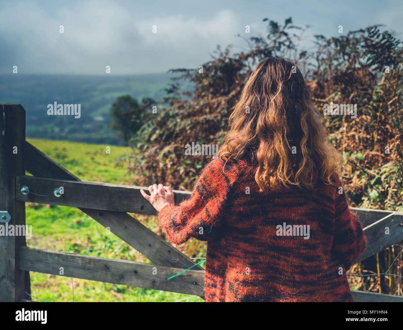 Eine junge Frau steht durch einen Zaun und Tor in der Landschaft Stockbild