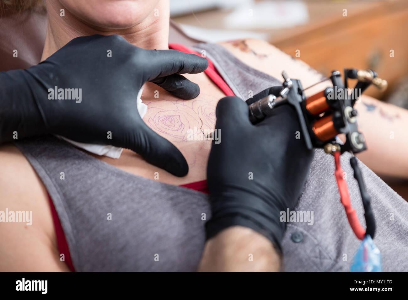 Close-up in die Hände eines erfahrenen Künstlers die Kontur einer Tätowierung Stockbild