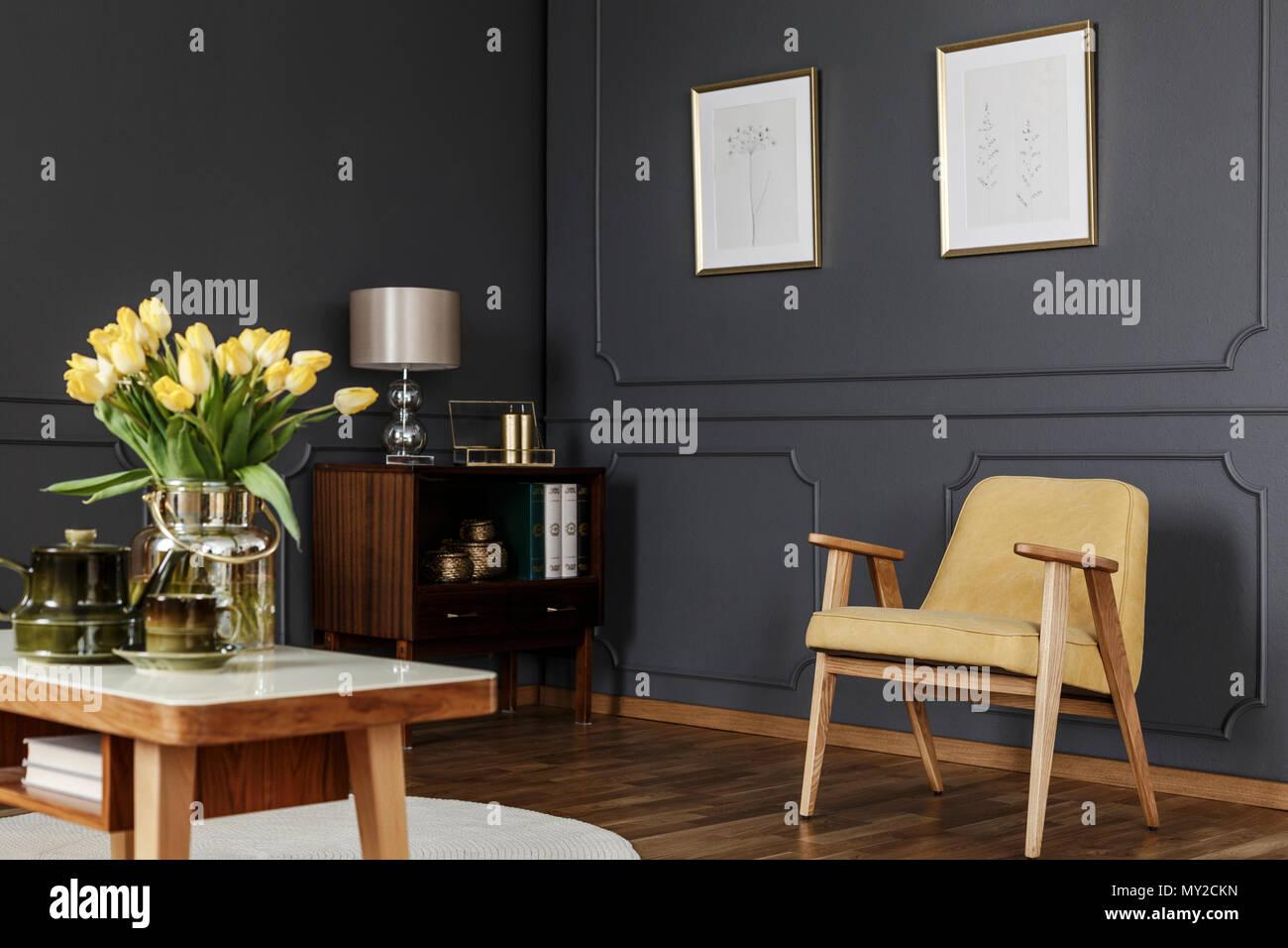 Holzgehäuse In Der Ecke Eines Dunklen Wohnzimmer Einrichtung Mit  Holztäfelung An Der Wand Mit Plakaten Neben Einem Gelben Sessel Und Tisch  Mit Tulpen.