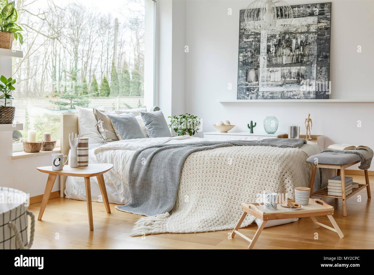 Ein Grosses Bett Mit Grau Kissen Gemalde An Der Wand Grosse Fenster Und Holzboden Im Gemutlichen Schlafzimmer Innenraum Stockfotografie Alamy