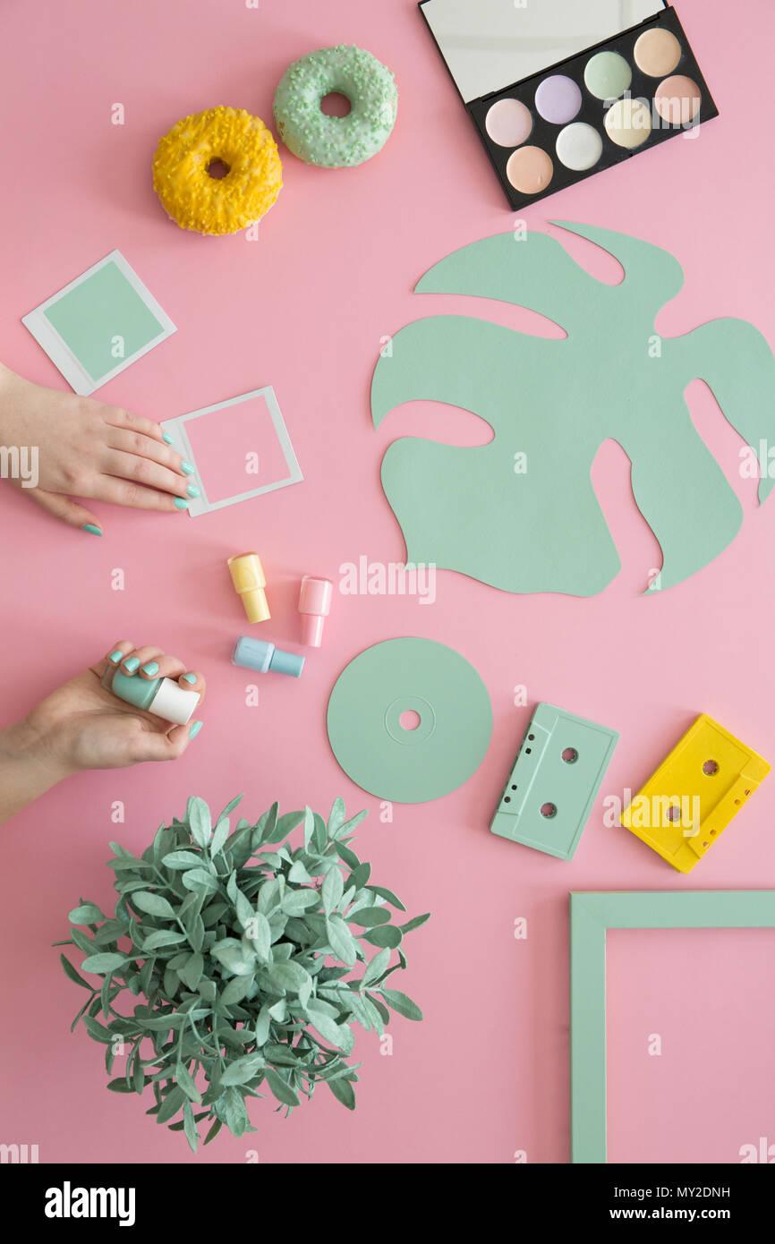 Frau mit grünen Nagellack am Schreibtisch mit Donuts, Make-up Palette, gelbe Kassette und Anlage Stockfoto