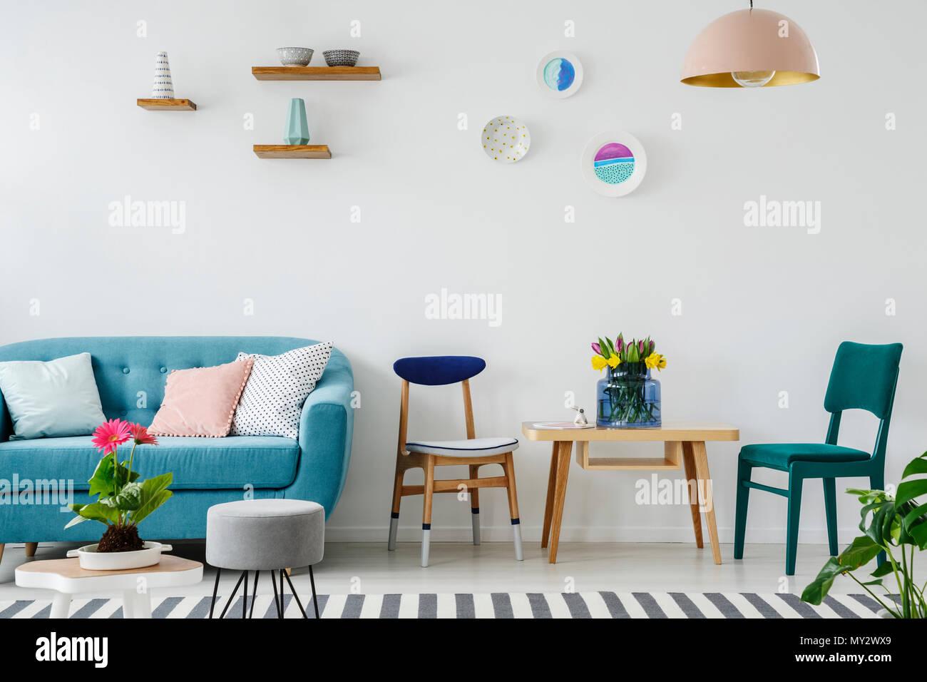 Blaue Couch Neben Einem Hölzernen Stuhl Am Tisch Mit Blumen Im