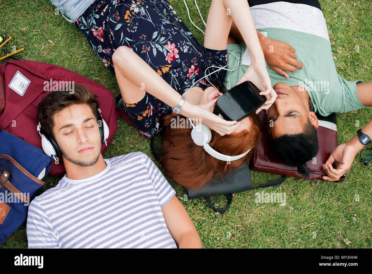 Freunde liegen auf Gras, mit Virtual reality Simulator und Hören mit Kopfhörern Stockfoto