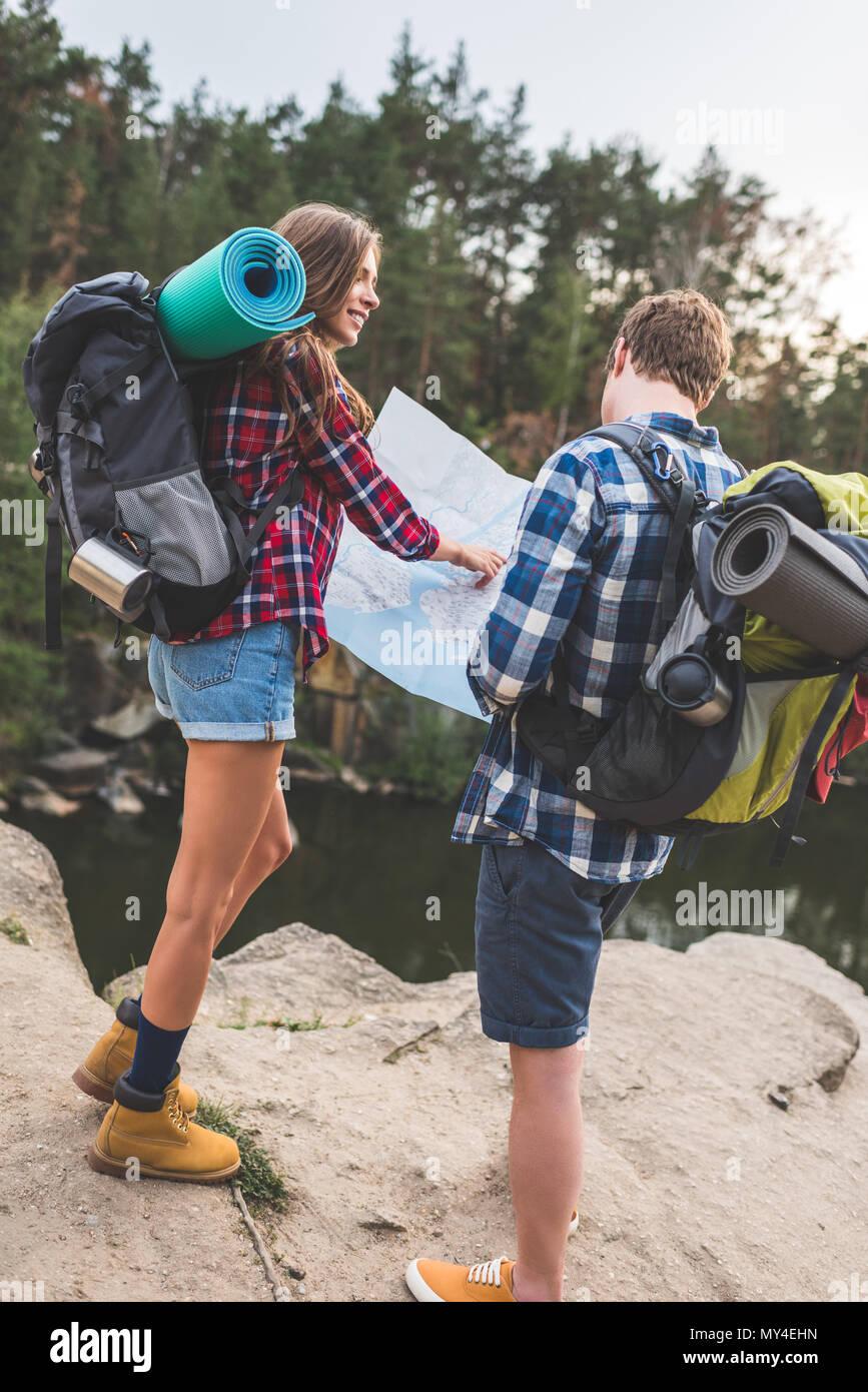 Aktive Paare mit Rucksäcken auf der Karte in der Nähe von Mountain Lake Stockbild