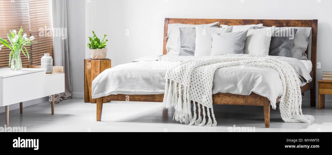 Holz- komfortables Bett mit vielen Kissen, Decke und Laken und einem ...