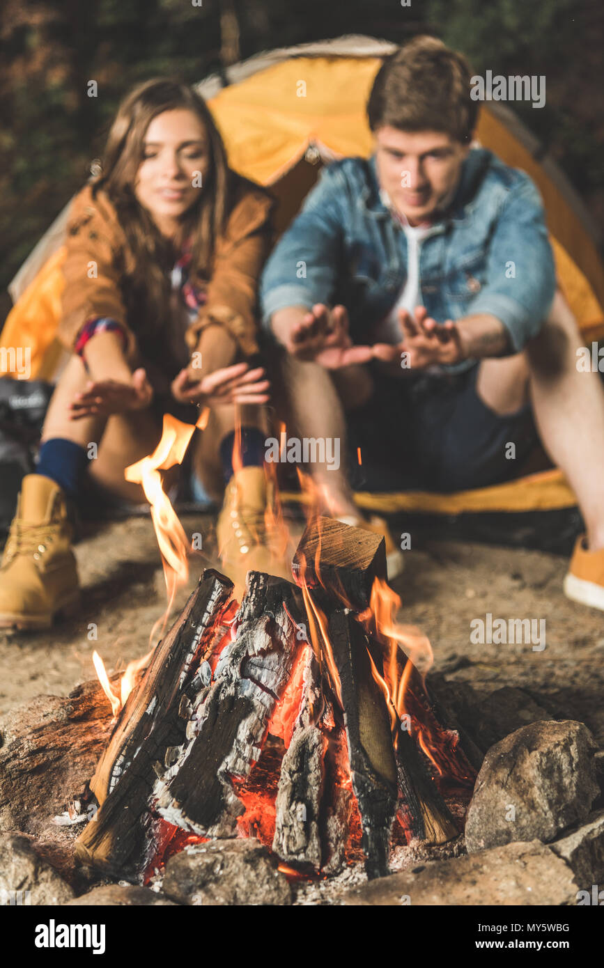 Paar wärmende Hände mit Lagerfeuer auf Wanderung Stockbild