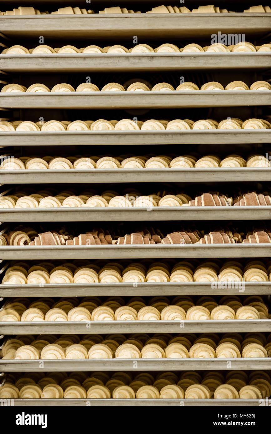 Raw Croissants auf Regalen in industriellen Ofen Stockbild