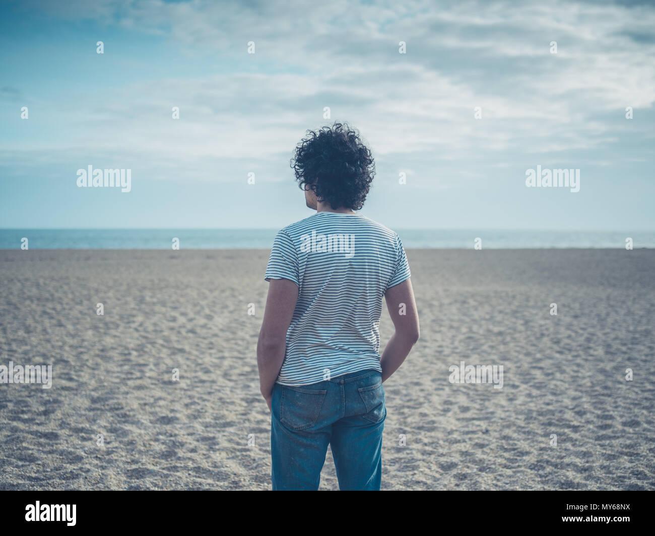 Ein junger Mann steht am Strand Stockbild